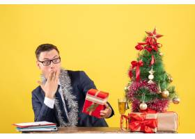坐在圣诞树旁的桌子旁黄色背景上的礼物_13361354