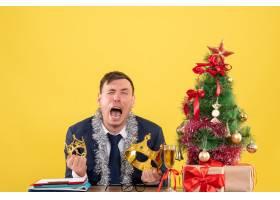 坐在圣诞树附近的桌子旁坐在黄色背景上的_13361608