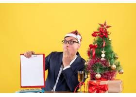 坐在圣诞树附近的桌子旁手持剪贴板的前景_13361348
