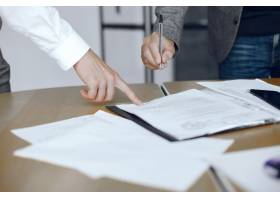 坐在律师办公桌前的生意人签署重要文件的_10701155