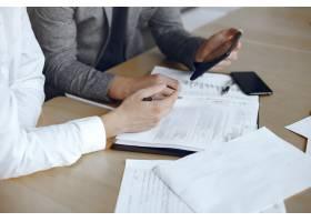 坐在律师办公桌前的生意人签署重要文件的_10701157