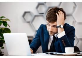 坐在笔记本前的年轻商人心烦意乱办公室背_7855209