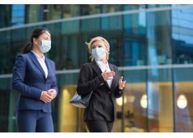 女商人们穿着工作服戴着口罩一起在城市_9648902