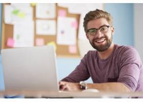 办公室里有笔记本电脑的快乐男士_13134043