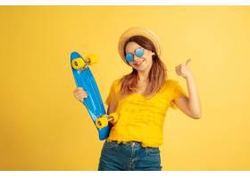 和滑板摆姿势黄色工作室背景上的高加索妇_13456761