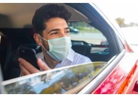 商人戴着口罩在开车上班的路上使用手机的_12682348