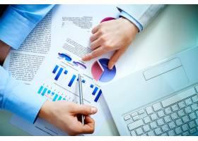 商人分析条形图和笔记本电脑的顶视图_854389