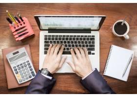 商务人士在木桌上用笔记本电脑或平板电脑工_1203664