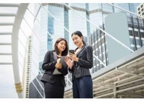 两个女商人站在办公室前用智能手机聊天商_1275671