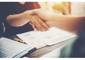 两位商务人士坐在工作场所握手的特写镜头_1185961