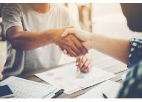 两位商务人士坐在工作场所握手的特写镜头_1185962