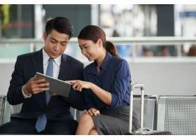 亚洲夫妇在机场使用平板电脑_5576854