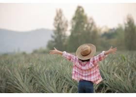亚洲女农民看到农场里长着菠萝年轻漂亮的_13013400
