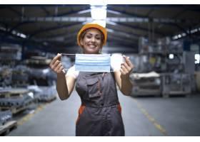 产业工人站在工厂大厅戴上卫生口罩以防_11034158