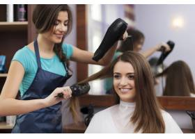 使用发刷和吹风机的女理发师_10896005