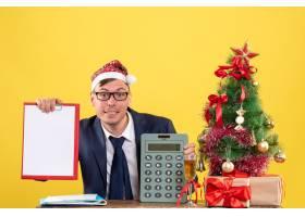 前景带着微笑的男人戴着圣诞帽坐在圣诞树_13361528