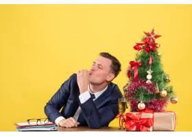 前景幸福的男人坐在圣诞树旁的桌子旁做着切_13361509