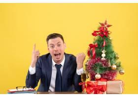 前景惊叹男子手指朝上坐在圣诞树旁的桌子_13361342
