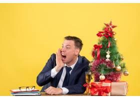 前景愤怒的男子坐在圣诞树附近的桌子旁大声_13361446