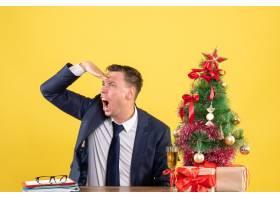前景愤怒的男子坐在圣诞树附近的桌子旁观察_13361402