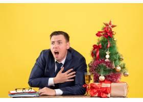 前景焦躁的年轻男子抱着胸膛坐在圣诞树旁的_13361328