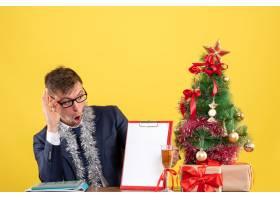 前视商务人员坐在圣诞树附近的桌子旁检查纸_13361543