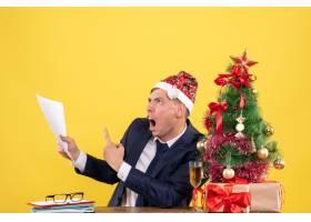 前视图愤怒的男子展示坐在圣诞树附近桌子上_13361451