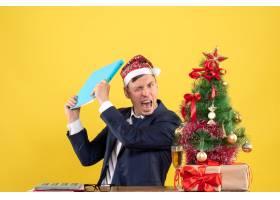 前视怒气冲冲的商人拿着文件文件坐在圣诞树_13361375