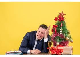 前视焦躁不安的男子紧闭双眼坐在圣诞树旁的_13361326