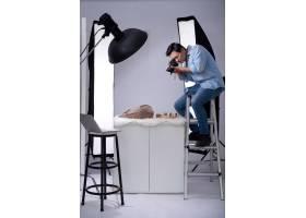 一位亚洲摄影师拿着相机坐在工作室的梯子上_5577542