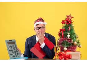 一位前视焦躁的商人拿着计算器坐在圣诞树旁_13361317