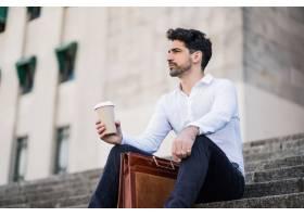 一位商人在下班休息时坐在户外的楼梯上喝着_13001863