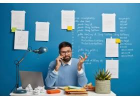 一位年轻的男性企业家在电话交谈中思考商业_12930511