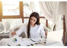 一位年轻的黑发女商人正在分析图表和操作笔_6449749