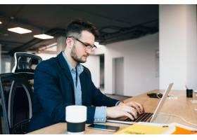 一位年轻的黑发男子正在办公室的桌子旁工作_9960957