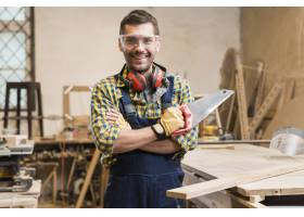 一位微笑的男木匠手持手锯看着相机的肖像_3579535