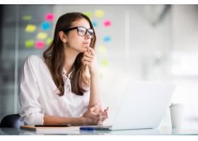 一位成功的女商人在办公室里穿着白衣在笔记_9909502