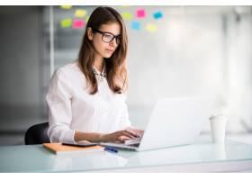 一位成功的女商人穿着白衣在办公室里用笔记_9909497