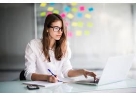 一位成功的女商人身着白衣在办公室里努力使_9909511