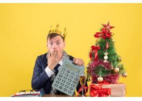 一位手持计算器的男子坐在圣诞树附近的桌子_13361346