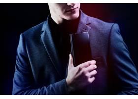 一位西装革履的商人正在给他的智能手机打洞_13301557