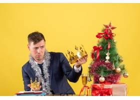 一名前视商人在比较坐在圣诞树附近桌子上的_13361555