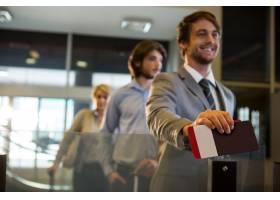 一名商人拿着登机牌站在办理登机手续的柜台_8236035