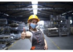 一名妇女站在工厂大厅竖起大拇指戴着卫_11034468