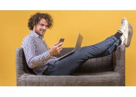一名男子在沙发上放着笔记本电脑_3622553