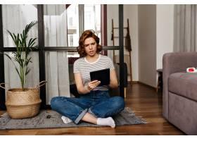 一名穿牛仔裤的女子坐在公寓的地板上带着_12677751
