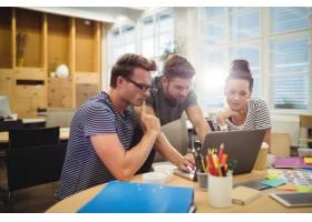 一群平面设计师在办公桌前讨论笔记本电脑_1006016