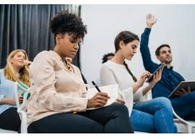 一群年轻人坐在一起开会同时举手提问业_10928846