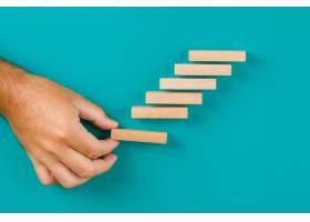 业务增长理念在绿松石桌上平铺手工堆放木_9485791