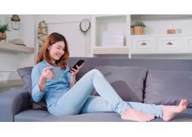 美丽迷人的微笑着的亚洲女人用智能手机端着_4014379